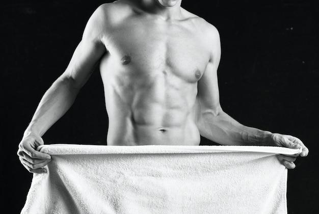 펌핑된 몸을 가진 남자가 수건 스튜디오 피트니스로 몸을 가립니다.