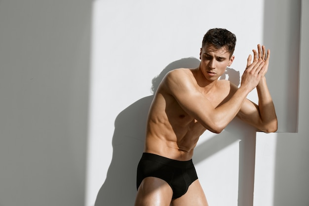 明るい背景のスタジオで黒いパンティーでポンプアップされた筋肉の体を持つ男