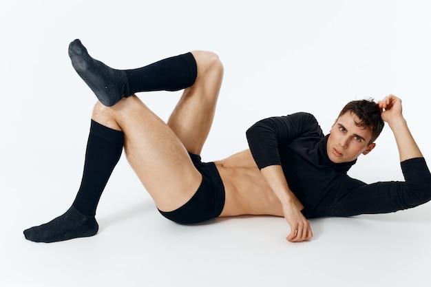 Мужчина с накачанным торсом и в трусах и носках свитера лежит на полу на свету.