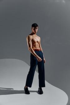 ジーンズとブーツで胴体をポンプでくみ上げた男が完全に成長している