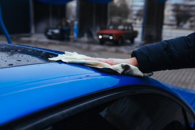 車を乾かすためのぼろきれを持った男。洗車のコンセプト