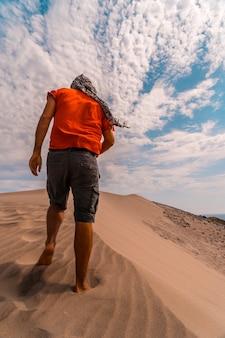 Мужчина в красной рубашке и тюрбане на голове гуляет по пустыне дюны
