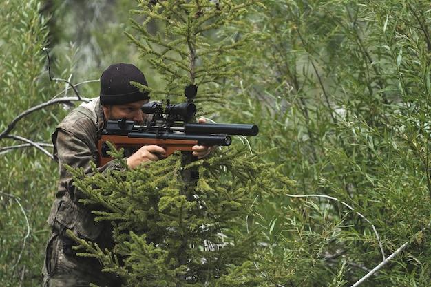 Мужчина с винтовкой сидит в засаде. снайпер готовится к стрельбе.