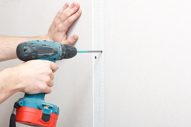 Мужчина с отверткой в руке крепит гипсокартон к стене