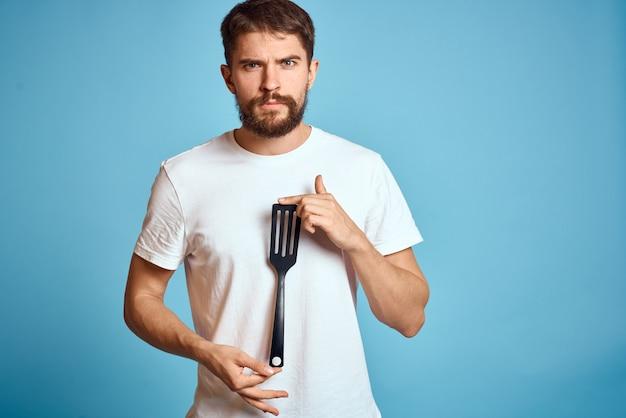 Человек с лопатой для приготовления пищи в руке на синем фоне