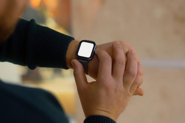 Мужчина с умными часами и макетом белого экрана на руке. мужчина использует фитнес-трекер на фоне торгового центра.