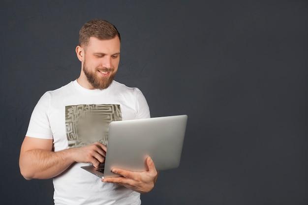 Человек с улыбкой и ноутбуком, на серой стене, в белой футболке и джинсах, с пространством для текста. концепция внештатный, бизнесмен, работает на ноутбуке и новые технологии.