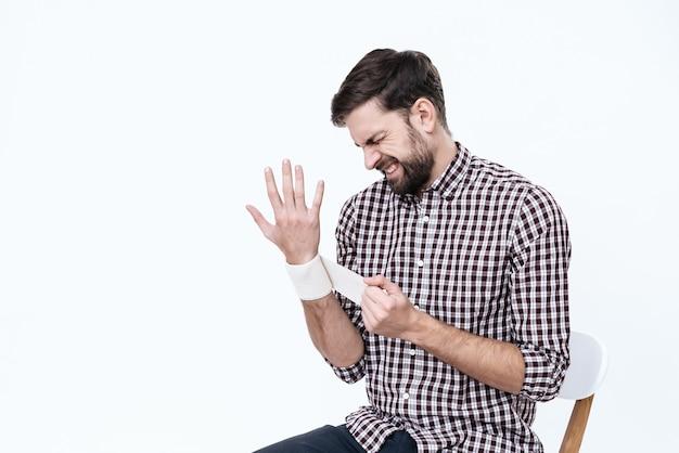 Человек с больной кистью перематывает свою кисть.