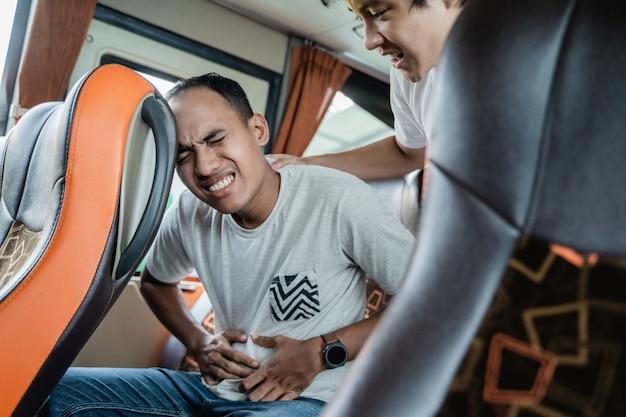 腹痛のある男性とその友人が旅行中にバスの座席に座って助けてくれた