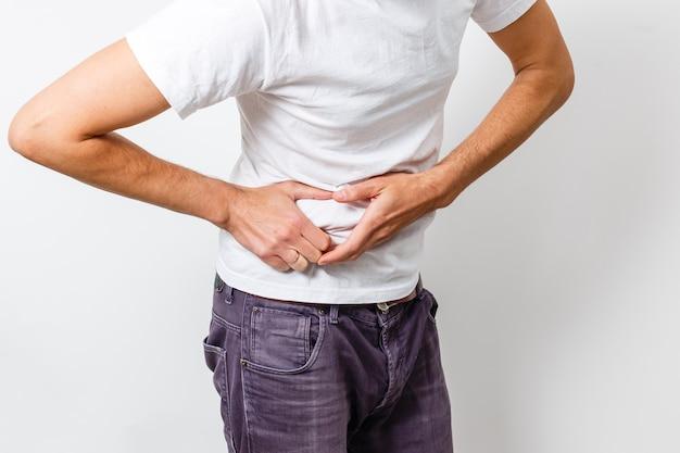 Мужчина с болью в животе в белой футболке дискомфорт пищеварение, несварение желудка
