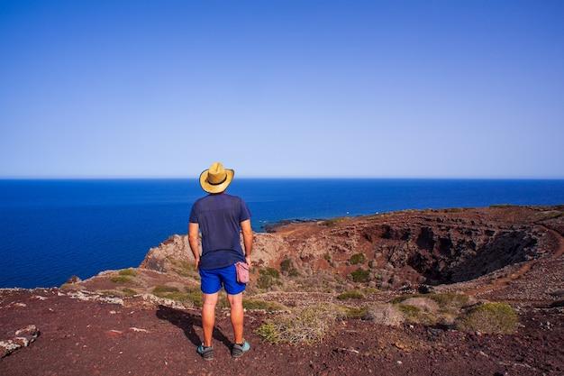 リノザ島のモンテネロと呼ばれる火山の頂上から海を見ている麦わら帽子をかぶった男。シチリア。イタリア