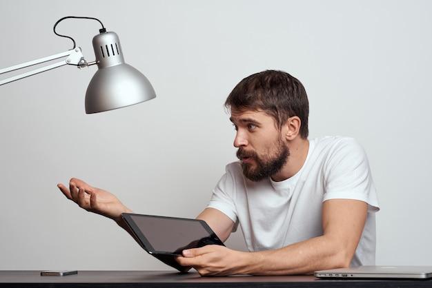 Мужчина с планшетом за столом жестикулирует руками на светлом фоне и железной лампой