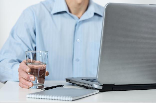 Мужчина с ноутбуком держит стакан воды.