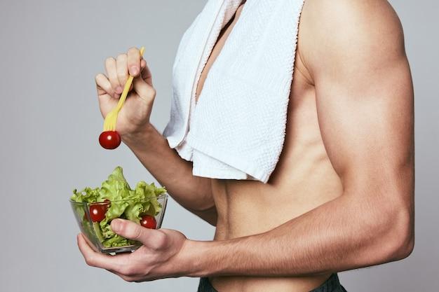 肩にタオルを持った男性がサラダの健康的な食事療法のプレート。