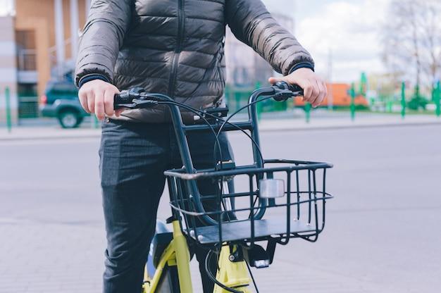 かごを持った黄色いレンタルシティバイクを持った男。