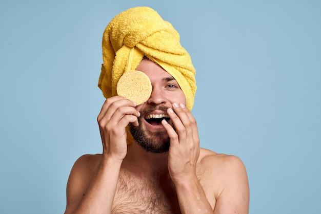 Мужчина с желтым полотенцем на голове оголил голые плечи, принимая душ.