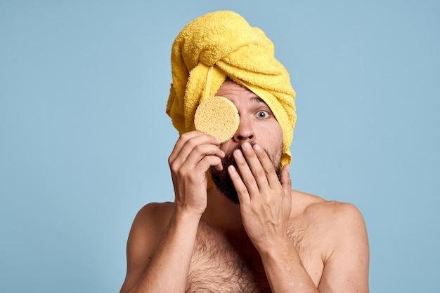 Мужчина с желтым полотенцем на голове, голые плечи, чистая кожа, принимает душ.