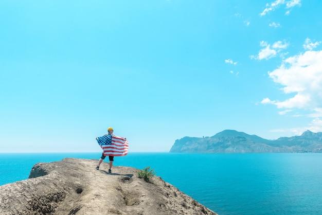 미국 국기를 든 남자가 산 정상에서 아름다운 바다를 바라보고 있다