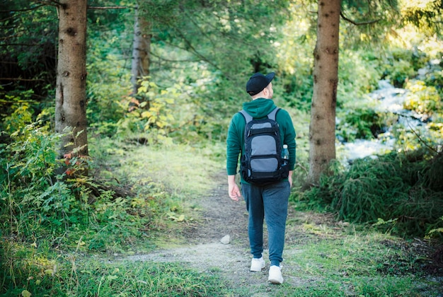 배낭을 메고 가을 숲을 걷는 남자. 가을 숲길을 따라 혼자 하이킹. 여행 개념입니다.