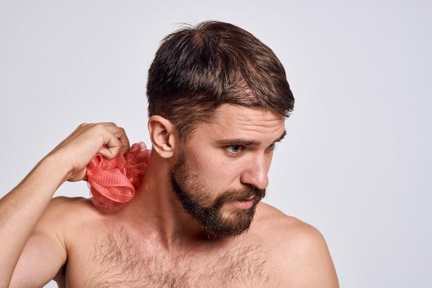 Мужчина с открытыми плечами и мочалкой в руках чистит кожу, принимая душ на светлом фоне. фото высокого качества