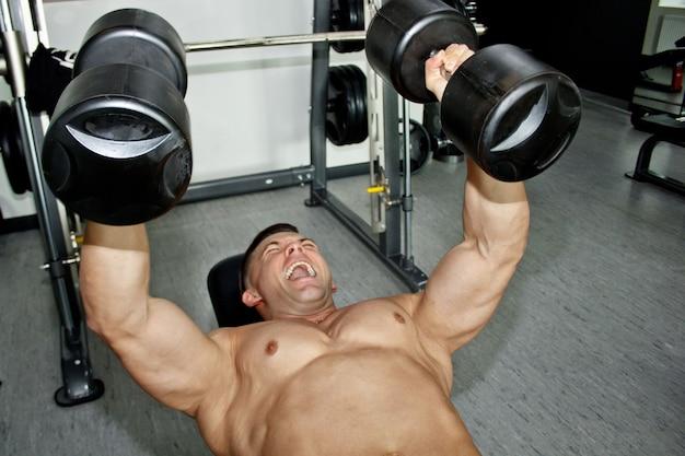 Мужчина с большими мускулами занимается тяжелой атлетикой в тренажерном зале. накачанный спортсмен занимается спортом на тренажерах-тяжеловесах. спортивные упражнения. яркие эмоции от работы на лице.