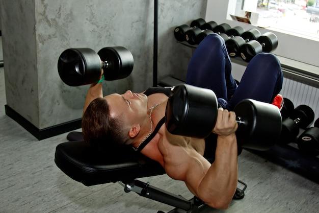 큰 근육을 가진 남자가 체육관에서 역도에 종사하고 있습니다. 펌핑 된 운동 선수가 헤비 웨이트 시뮬레이터로 스포츠를 시작합니다. 스포츠 연습.