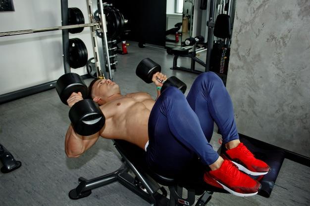 Мужчина с большими мускулами занимается тяжелой атлетикой в тренажерном зале. накачанный спортсмен занимается спортом на тренажерах-тяжеловесах. спортивные упражнения.