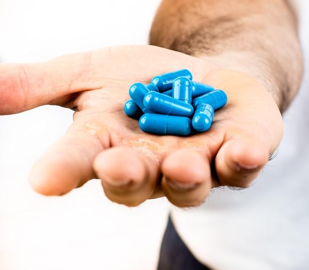 青い薬または白い背景を持つ彼の手に栄養補助食品カプセルを持つ男
