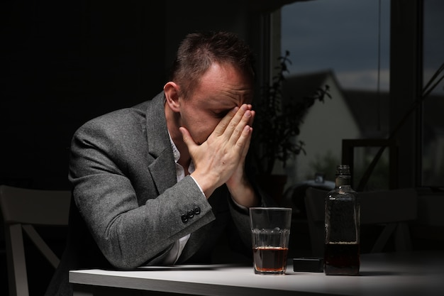 キッチンでウイスキーのボトルを持つ男。飲酒とアルコール依存症の概念。アルコールの父。悲しみに疲れた病人が一人で飲む。感情的な経験。セレクティブフォーカス