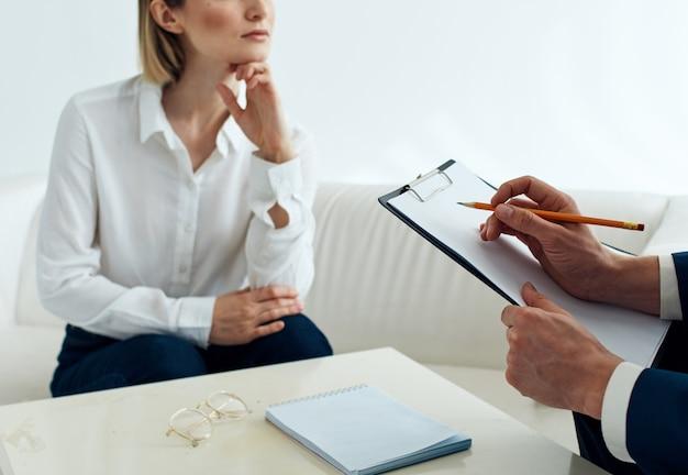 문서가있는 남자와 실내 테이블에서 소파에 여자 직원 심리학자 접수 의사