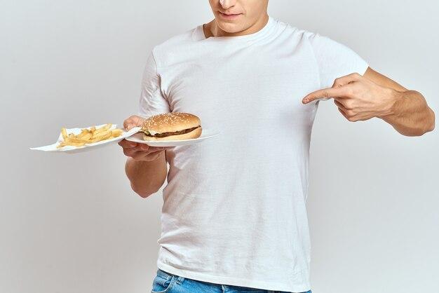 Мужчина с картошкой фри и гамбургером