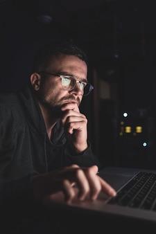 暗闇の中で眼鏡をかけている男性がコンピューターの画面、コピースペースを見ています。