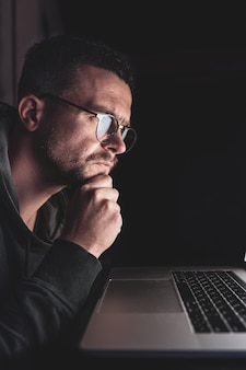 眼鏡をかけた男が夜遅くにコンピューターで働いている