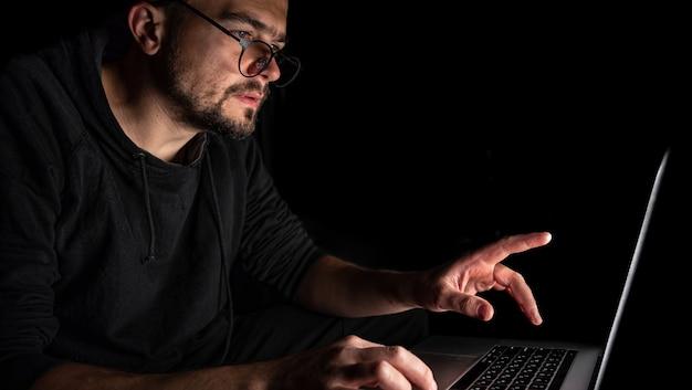眼鏡をかけた男が暗闇の中でラップトップで働いています