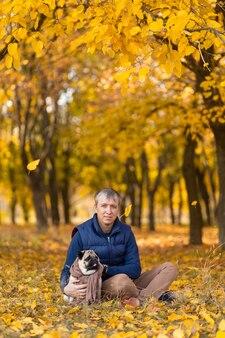 Мужчина со своей любимой мопсой на прогулке осенью в парке.