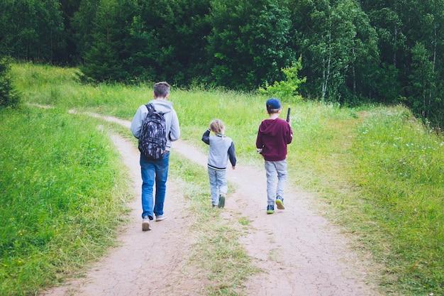 딸과 아들을 둔 남자가 하이킹 여행 중에 여름 숲의 길을 걷고 있습니다.