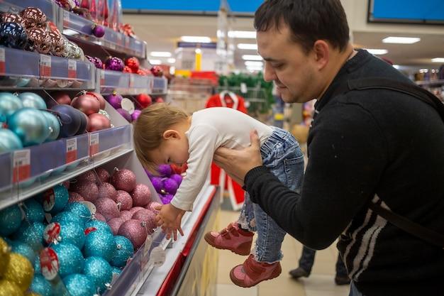 Мужчина с любовной улыбкой держит на руках маленького милого ребенка в магазине рождественских новогодних украшений для елки. ребенок висит в руках отца. крупный план, мягкий фокус, размытие фона