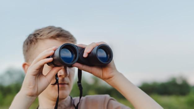 하늘과 푸른 숲에 대해 현대 쌍안경을 가진 남자. 사냥, 여행 및 야외 레크리에이션의 개념. 복사 공간이 있는 배너입니다. 여행자나 사냥꾼이 쌍안경을 통해 관찰하고 있습니다.