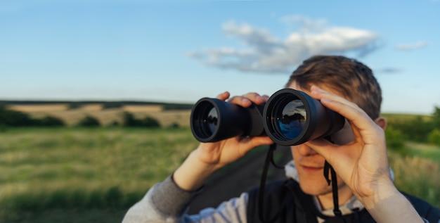 하늘과 푸른 언덕에 대하여 현대 쌍안경을 가진 사람. 사냥, 여행 및 야외 레크리에이션의 개념.