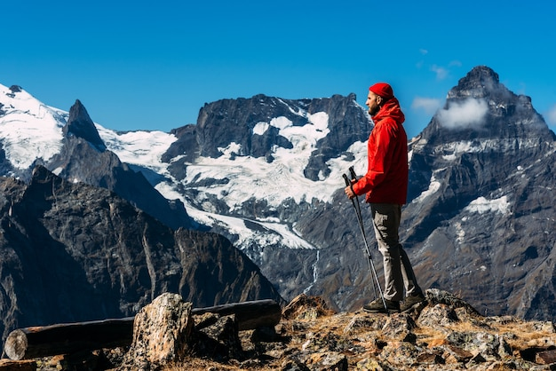 山にノルディックウォーキングの棒を持った男。コーカサスを旅する男。マウンテンスポーツ。マウンテンツーリズム。徒歩旅行。山への旅。山々の間を歩くノルディックウォーキング。
