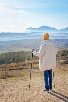 ノルディックウォーキングの棒を持った男が山の高いところに立っています。後ろからの眺め。