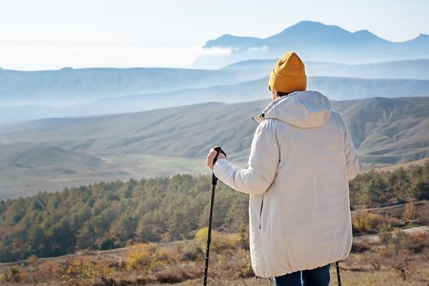 노르딕 워킹 스틱을 가진 남자가 산에 우뚝 서 있습니다. 뒤에서 봅니다.