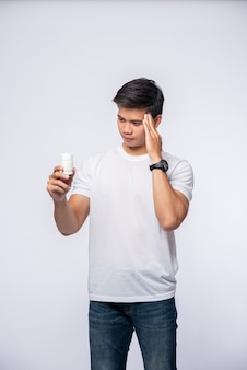 Мужчина с болью в руке держит бутылку с лекарством, а другую руку держит на голове.