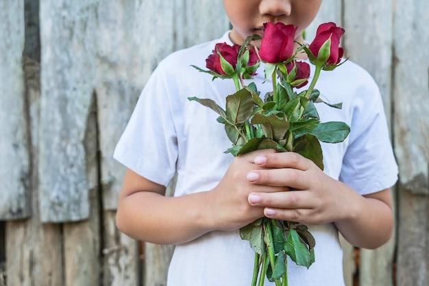 赤いバラとバレンタインの日の手の中にバレンタインを持つ男