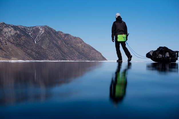 Человек с кувалдами зимой гуляет по озеру с зеркальным льдом