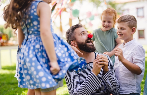 여름에 정원에서 야외 바닥에 앉아 놀고 있는 어린 아이들을 둔 남자.