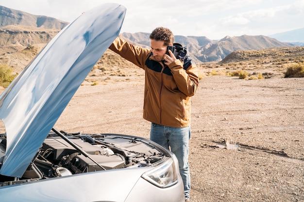 사막 한가운데서 스마트 폰으로 통화하는 자동차 후드를 연 남자