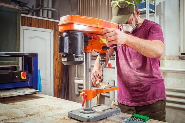 Мужчина в рабочей одежде и фуражке плотника вырезает деревянную доску на большом сверлильном станке оранжевого цвета.