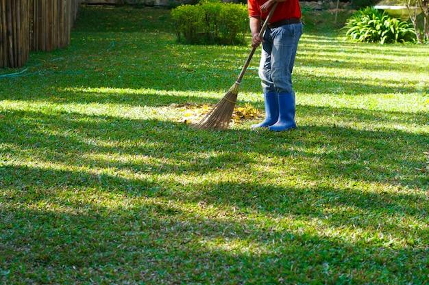 公共の公園で葉っぱを掃除する男性労働者