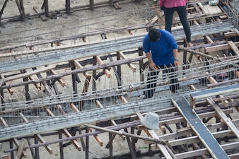 A man workiing with rebar steel reinforcement in beam concrete structure of home building